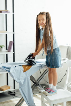 pre-adolescent kid burning shirt with iron at home