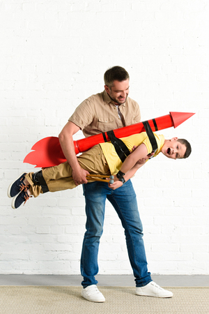 father holding son with toy rocket on back at home Banco de Imagens