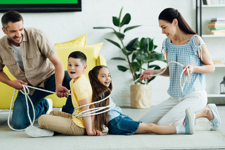 smiling parents tying children with rope at home, parenthood concept Stok Fotoğraf