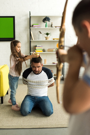 disobedient children playing with tied father and pretending shooting with toy bow at home