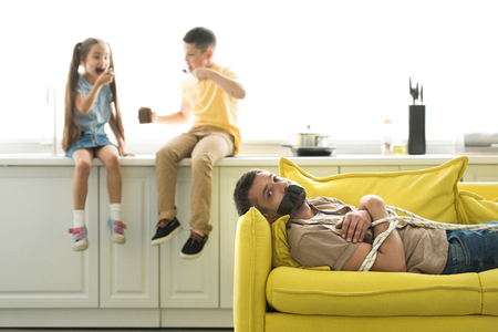 children eating chocolate and father lying tied on sofa at home