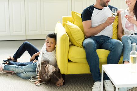 parents drinking wine and tied children lying on floor at home, parenthood concept