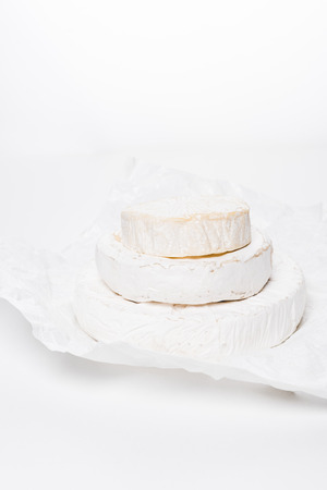 stack of tasty brie cheese heads on crumpled paper and on white surface