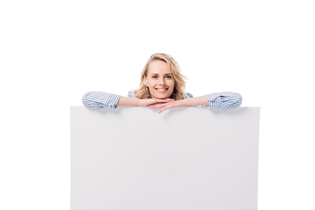 smiling attractive woman leaning on blank placard isolated on white Stock Photo