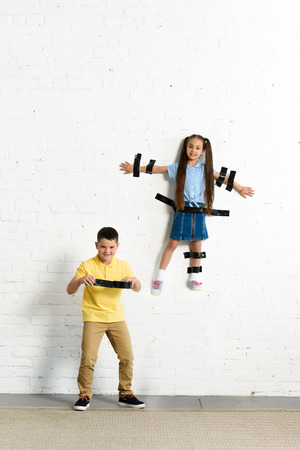 brother glued sister to wall with black tape at home Banco de Imagens