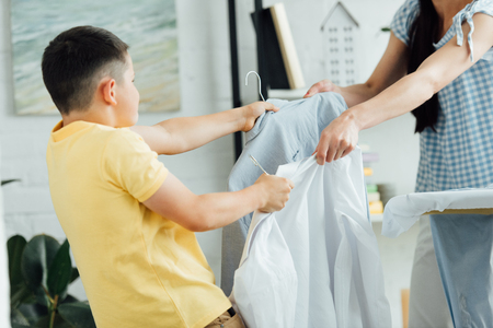 cropped image of mother and son holding rags with shirts