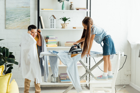 disobedient siblings ironing clothes at home Banco de Imagens