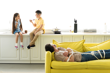 children eating chocolate at kitchen and father lying tied on sofa Imagens