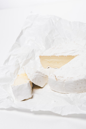 close-up shot of sliced brie cheese on crumpled paper and on white surface