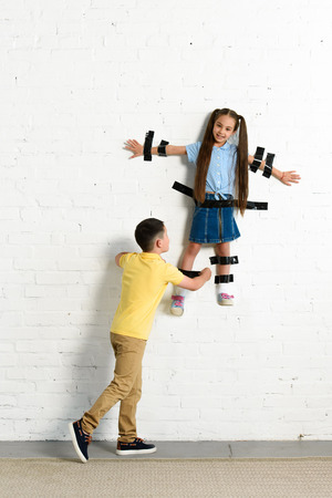brother gluing sister to wall with black tape at home Banco de Imagens