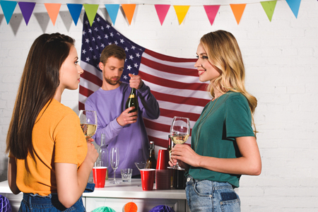 beautiful young women holding glasses of wine and looking at each other while man opening wine bottle behind