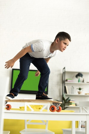 pre-adolescent boy standing on skateboard on table at home