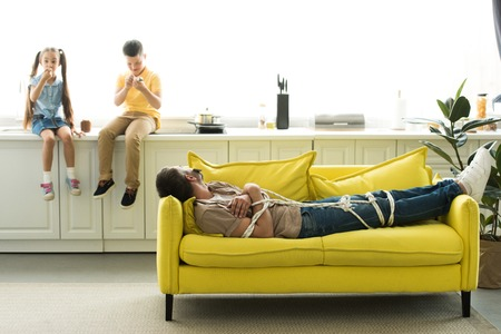 children eating dessert and father lying tied on sofa at home, parenthood concept
