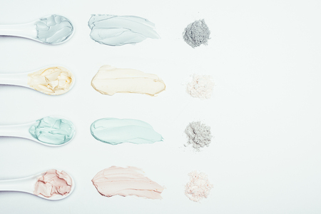 flat lay with spoons, clay powder and colorful clay mask smudges placed in row on white surface