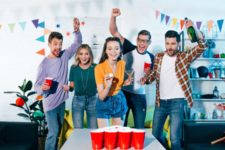 happy young friends looking at smiling girl playing beer pong at home party