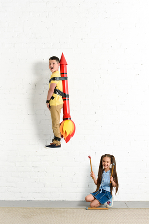sister pretending setting on fire toy rocket with brother at home Banco de Imagens