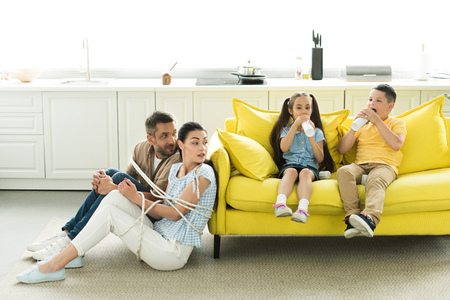 tied parents sitting near sofa and children eating dessert at home Фото со стока