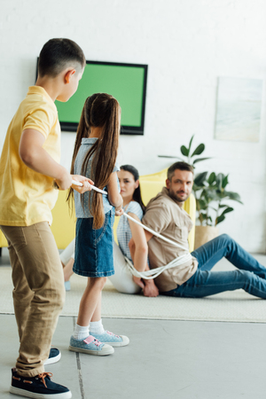 kids tying parents with rope on floor at home