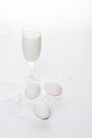 chicken eggs with flour and milk on white surface