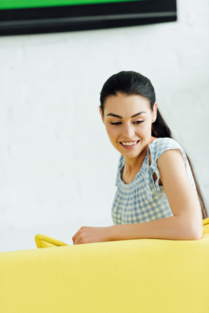 attractive woman sitting on yellow sofa at home and looking down 스톡 콘텐츠