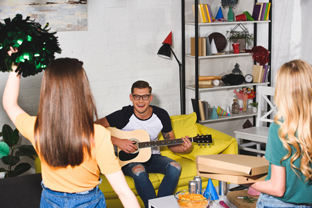 back view of girls with pizza boxes and pom-poms looking at smiling man playing guitar at home party