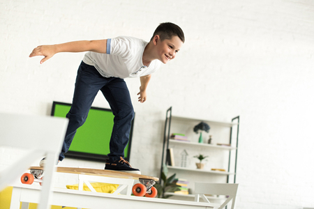 smiling pre-adolescent boy standing on skateboard on table at home