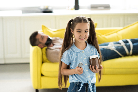 father lying tied on sofa and smiling daughter holding chocolate at home