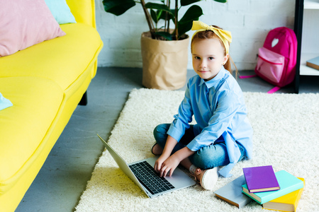 high angle view of beautiful child using laptop and looking at camera at home Stock Photo