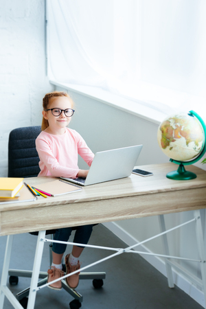 high angle view of child in eyeglasses smiling at camera while using laptop and studying at home Stock Photo