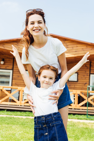 mother and daughter in white t-shirts in front of wooden cottage