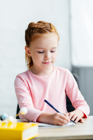 beautiful smiling schoolgirl sitting at desk and taking notes Stock Photo