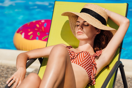 attractive young woman in straw hat relaxing on sun lounger at poolside Фото со стока