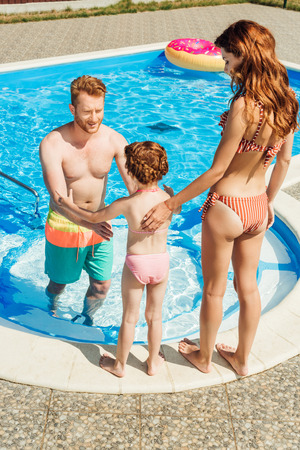 beautiful young family spending time together at poolside