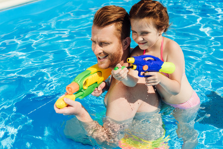 handsome father and adorable daughter playing with water guns in swimming pool Stock Photo