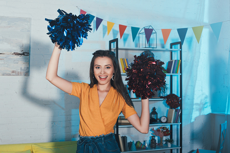 beautiful young woman holding pom-poms and smiling at camera at home party Stock Photo