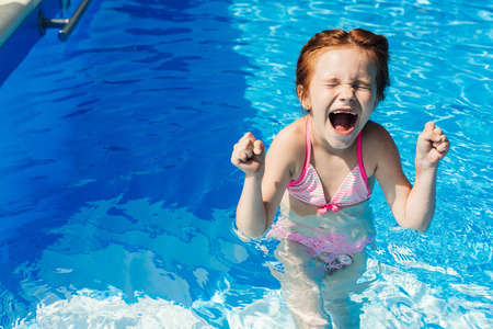 screaming little child in bikini in swimming pool Imagens