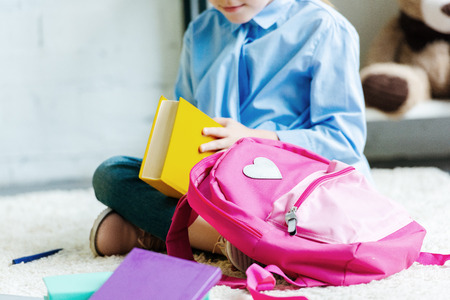 cropped shot of smiling child holding book while packing school bag