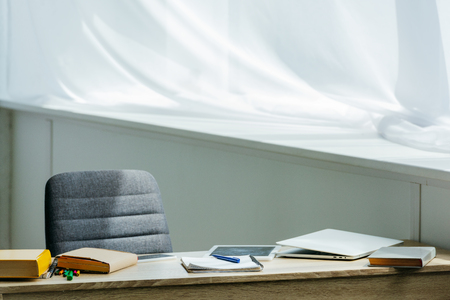 digital tablet, laptop and books on wooden table