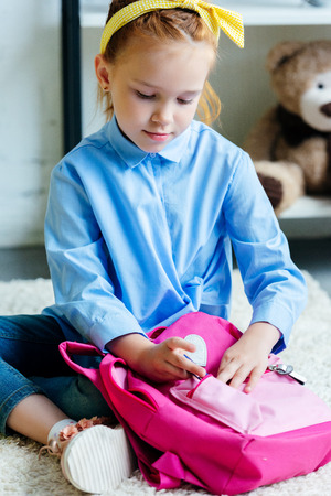 adorable child packing pink school bag at home Stock Photo