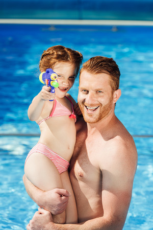 happy father and daughter with water gun embracing in swimming pool and looking at camera