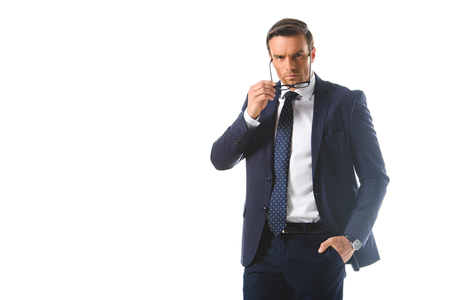 serious businessman with hand in pocket putting on eyeglasses isolated on white background Standard-Bild - 106080234
