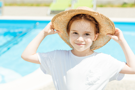 adorable little child in straw hat in front of swimming pool