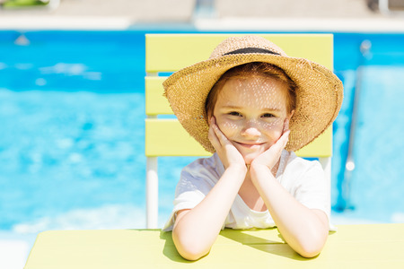 adorable little child in straw hat sitting on chair in front of swimming pool