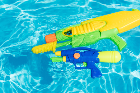 plastic colorful water pistols floating in swimming pool