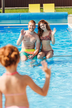 rear view of little girl waving to parents at swimming pool Stock Photo
