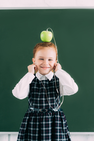 adorable little schoolgirl with apple on head and earphones smiling and looking at camera