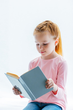 adorable red haired kid reading book while sitting on windowsill Stock Photo