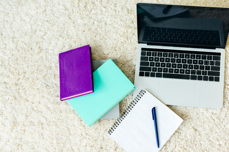 top view of books, notebook with pen and laptop with blank screen on carpet Stock Photo
