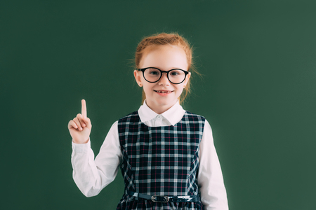 adorable little schoolgirl in eyeglasses pointing with finger and smiling at camera while standing near blackboard