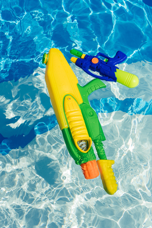 plastic colorful water guns floating in swimming pool Stock Photo